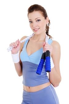 Piękna młoda kobieta szkolenia z skakanka na białym tle