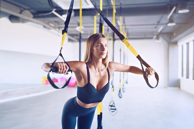 Piękna młoda kobieta szkolenia z zawiesiem trenera zawiesia lub pasy do zawieszenia w siłowni. koncepcja ćwiczeń górnej części ciała na trx.