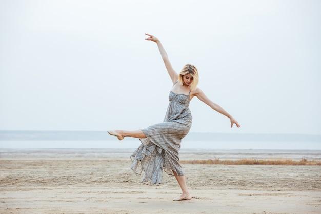 Piękna młoda kobieta tancerka w długiej sukni tańczy boso na plaży
