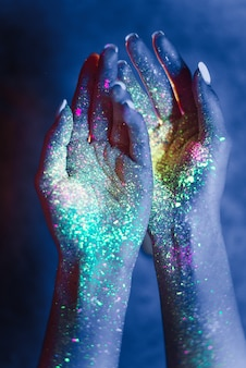 Piękna młoda kobieta tańczy i robi imprezie z fluorescencyjnym obrazem na twarzy. neonowe portrety twarzy