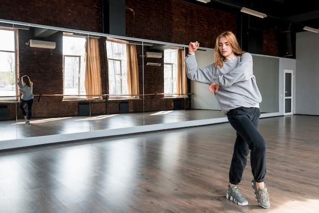 Piękna młoda kobieta tańczy przed lustrem