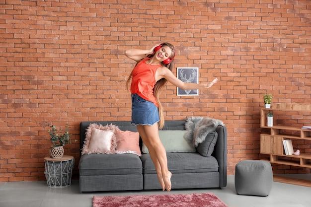 Piękna młoda kobieta tańczy w domu