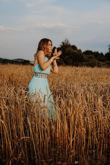 Piękna młoda kobieta tańczy w polu o zachodzie słońca