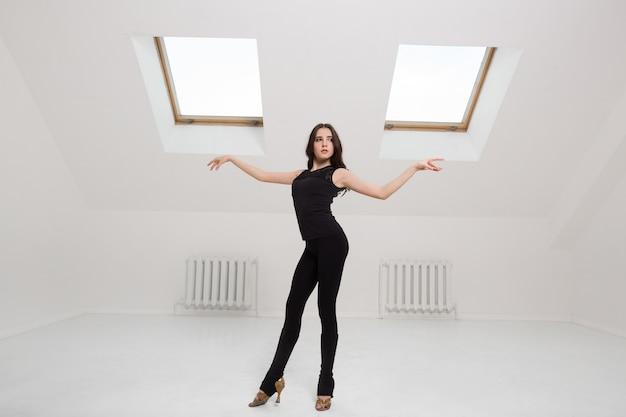 Piękna młoda kobieta tańczy w studio