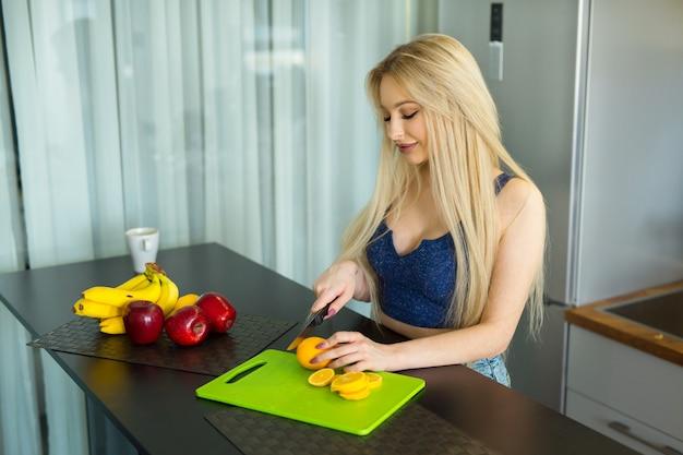 Piękna młoda kobieta tnie owoce w kuchni