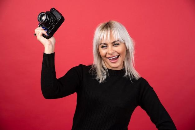 Piękna młoda kobieta trzyma aparat, stojąc na czerwonym tle. wysokiej jakości zdjęcie