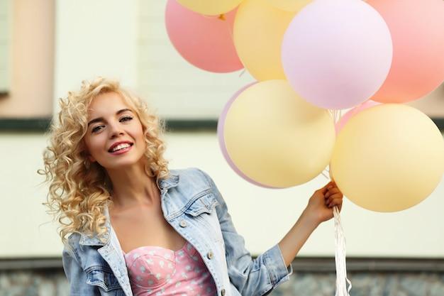 Piękna młoda kobieta trzyma balony na ulicy