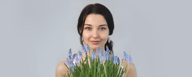 Piękna młoda kobieta trzyma bukiet wiosennych kwiatów w rękach