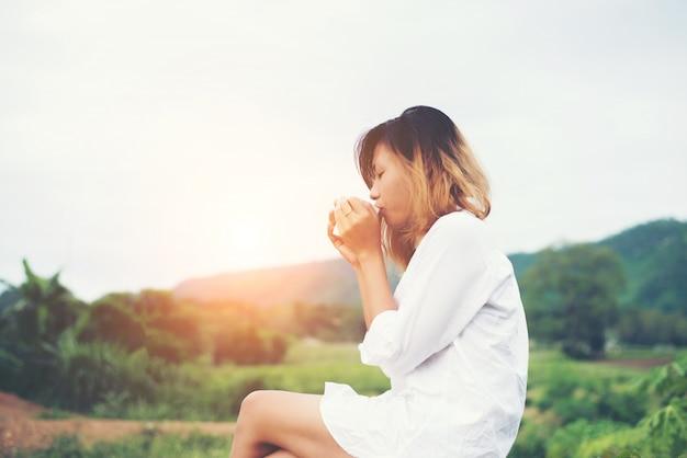 Piękna młoda kobieta trzyma kawę siedząc na