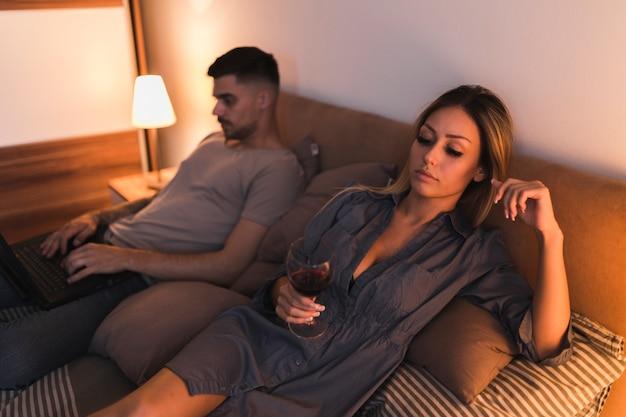 Piękna młoda kobieta trzyma kieliszek do wina leżącego z mężem