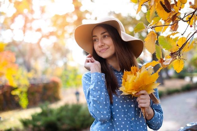 Piękna młoda kobieta trzyma kilka jesiennych liści. wspaniała młoda kobieta jesienią