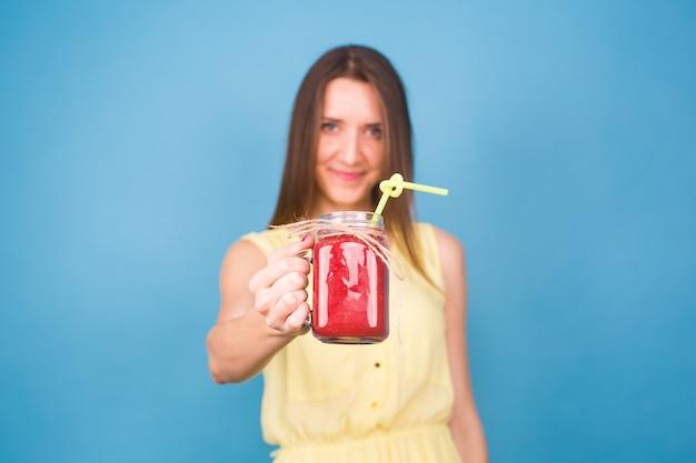 Piękna młoda kobieta trzyma koktajl truskawkowy na niebiesko. koncepcja zdrowych napojów ekologicznych. osoby na diecie.