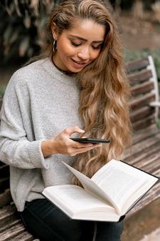 Piękna młoda kobieta trzyma książkę podczas gdy sprawdzać jej telefon