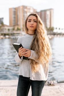 Piękna młoda kobieta trzyma książkę poza