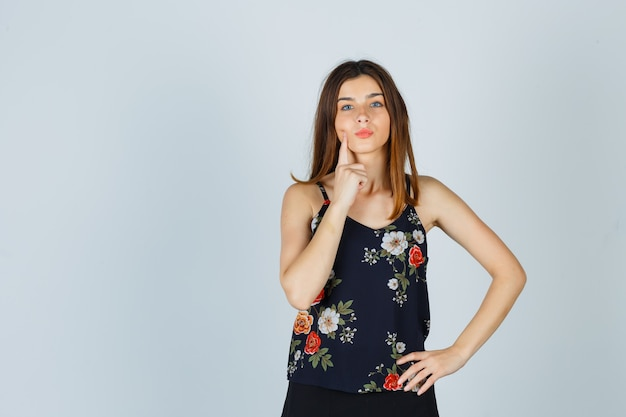 Piękna młoda kobieta trzyma palec na policzku, wydymając usta w bluzce