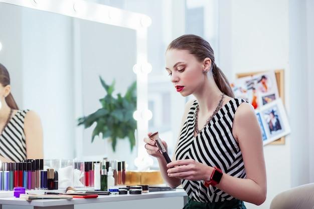 Piękna młoda kobieta trzyma pędzel do makijażu podczas nakładania makijażu