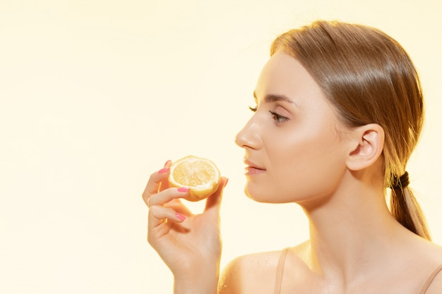 Piękna młoda kobieta trzyma plasterek cytryny