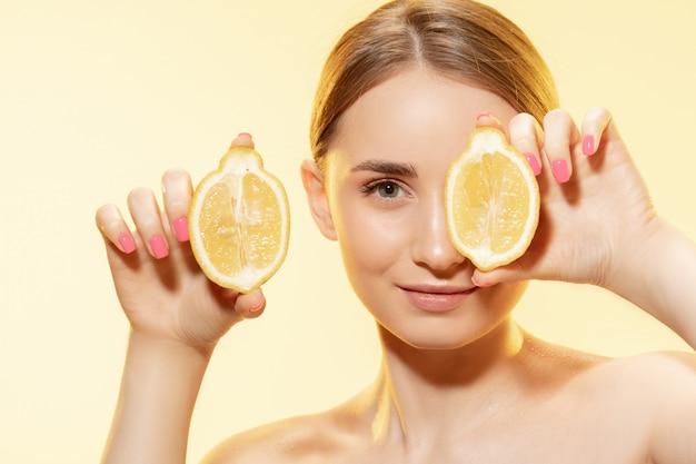 Piękna młoda kobieta trzyma plasterki cytryny