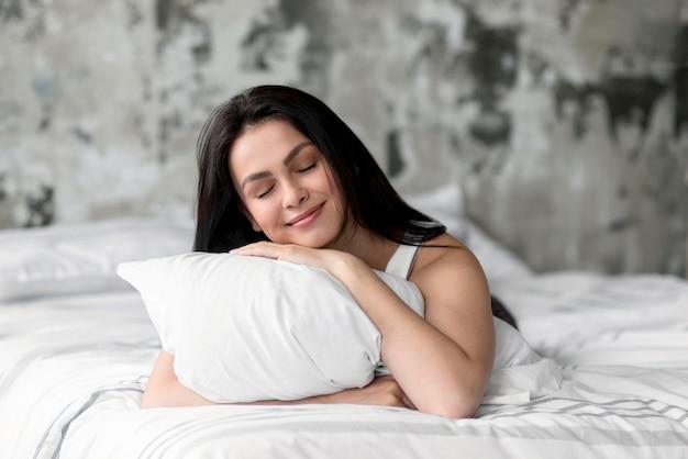 Piękna młoda kobieta trzyma poduszkę