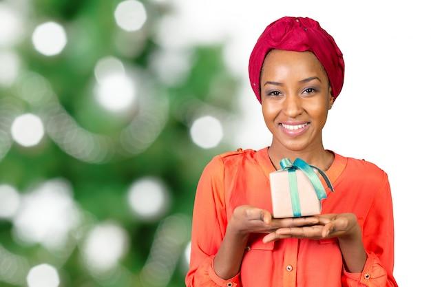 Piękna młoda kobieta trzyma prezent