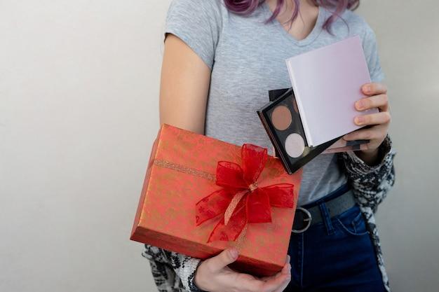 Piękna młoda kobieta trzyma pudełko z palet kosmetycznych, studio strzał na szarym tle. skopiuj miejsce