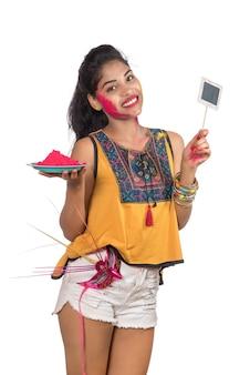 Piękna młoda kobieta trzyma pudrowany kolor w talerzu z maską karnawałową i małą tablicą z okazji festiwalu holi.