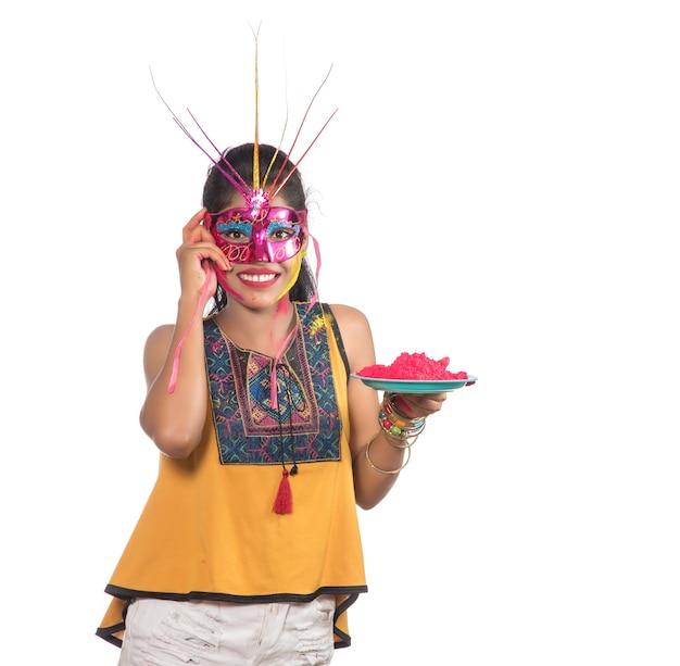 Piękna młoda kobieta trzyma pudrowany kolor w talerzu z maską karnawałową z okazji festiwalu holi.