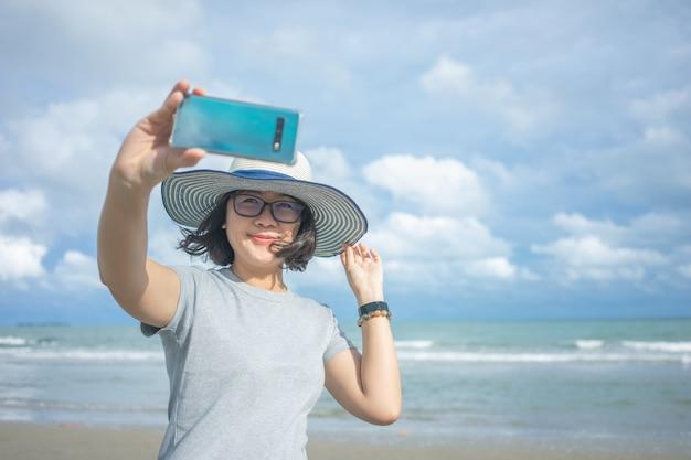 Piękna młoda kobieta trzyma smartphone