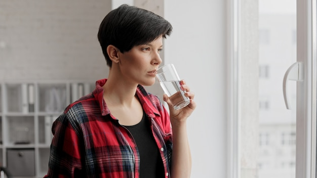 Piękna młoda kobieta trzyma szklankę wody i picia. opieka zdrowotna, dieta. zdrowe odżywianie.