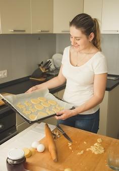 Piękna młoda kobieta trzyma tacę z surowymi ciasteczkami
