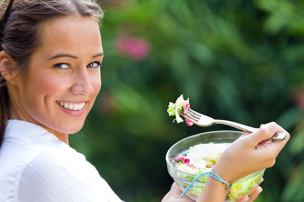 Piękna młoda kobieta trzyma zielonej sałatki, outdoors