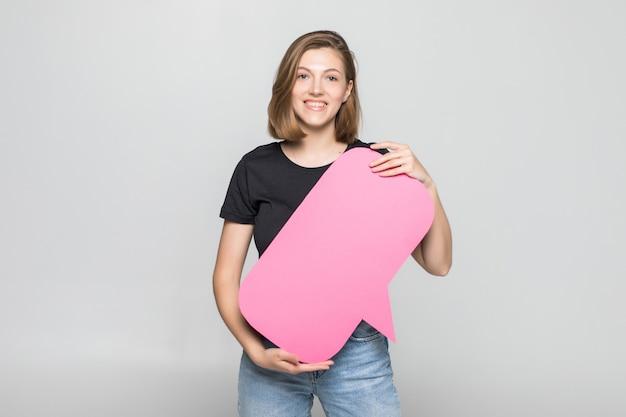 Piękna młoda kobieta trzymając pusty dymek na szarej ścianie