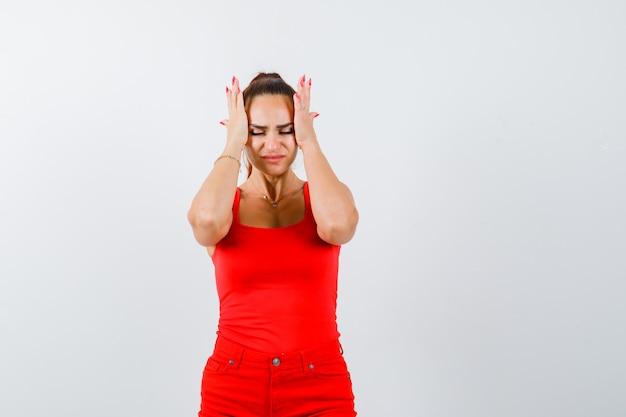 Piękna młoda kobieta trzymając się za ręce na głowie w czerwony podkoszulek, spodnie i patrząc przygnębiony, widok z przodu.