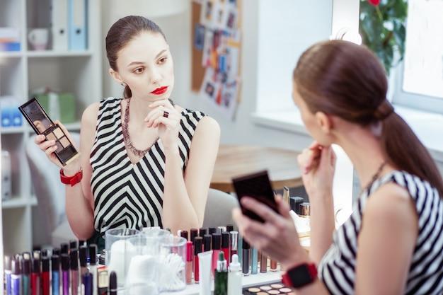 Piękna młoda kobieta trzymająca cień do powiek, patrząc w lustro