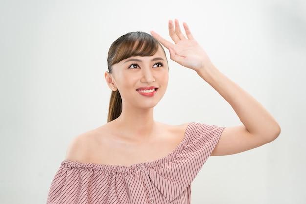 Piękna młoda kobieta trzymająca rękę na czole