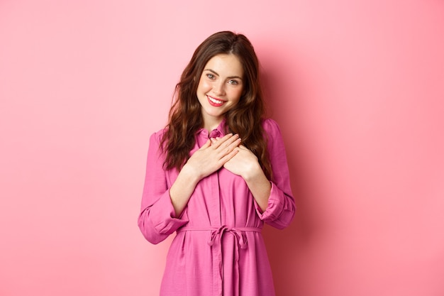 Piękna młoda kobieta trzymająca się za ręce na sercu i uśmiechnięta wdzięczna, wyrażająca wdzięczność, dziękując, otrzymująca serdeczny prezent, stojąc nad różową ścianą.