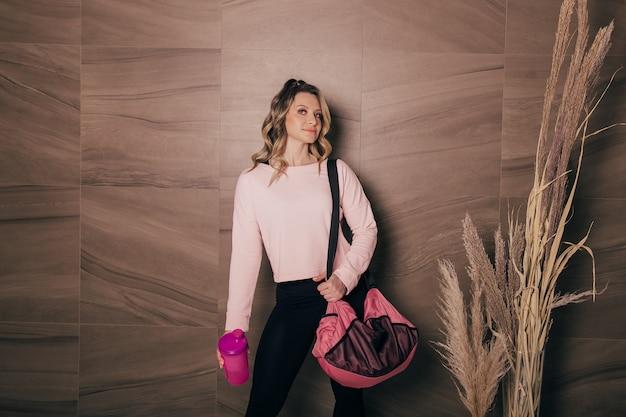 Piękna młoda kobieta trzymająca torbę sportową i butelkę wody