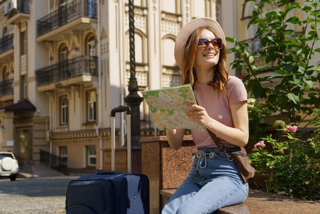 Piękna młoda kobieta turysta przyjemny z mapą miasta i walizką w centrum miasta.