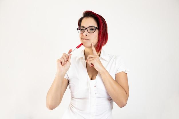 Piękna młoda kobieta ubrana w białą bluzkę i okulary myśli o nowych innowacyjnych pomysłach