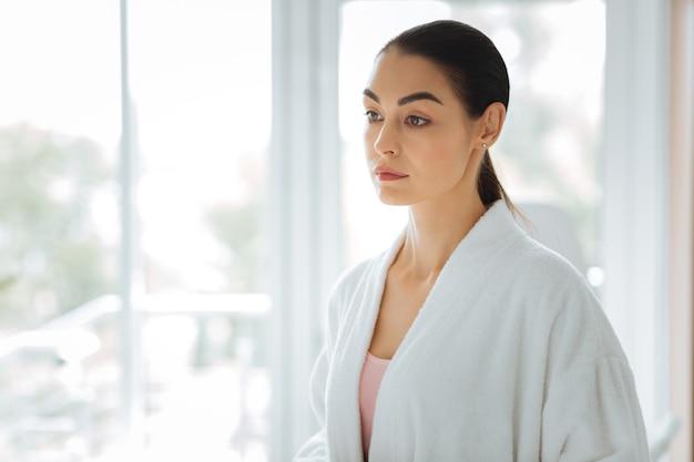 Piękna młoda kobieta ubrana w białą szatę, przygotowując się do zabiegu w gabinecie kosmetycznym