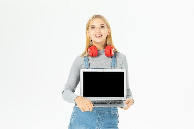 Piękna młoda kobieta ubrana w czerwone słuchawki, pokazując jej wyświetlacz laptopa