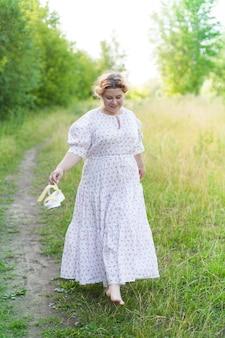 Piękna młoda kobieta ubrana w elegancką białą sukienkę stojącą z uśmiechem na drodze w lesie z promieniami słońca promieniującymi przez liście drzew