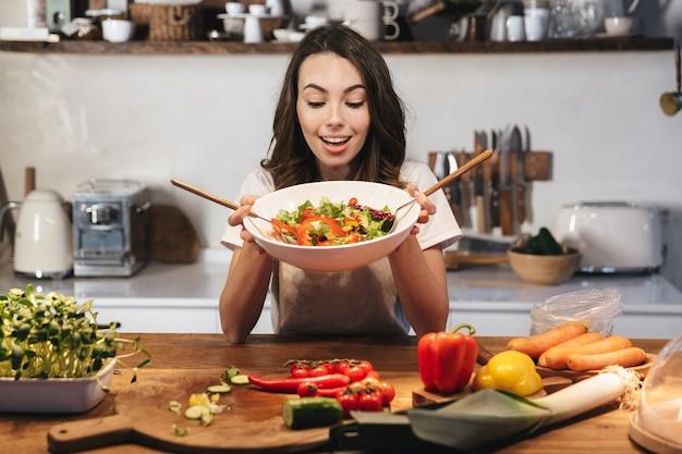 Piękna młoda kobieta ubrana w fartuch gotowanie zdrowej sałatki w kuchni w domu, mieszanie