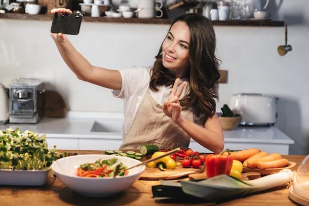 Piękna młoda kobieta ubrana w fartuch, gotowanie zdrowej sałatki w kuchni w domu, przy selfie z telefonem komórkowym