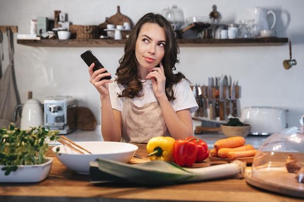 Piękna młoda kobieta ubrana w fartuch, gotowanie zdrowej sałatki w kuchni w domu, przy użyciu telefonu komórkowego podczas gotowania