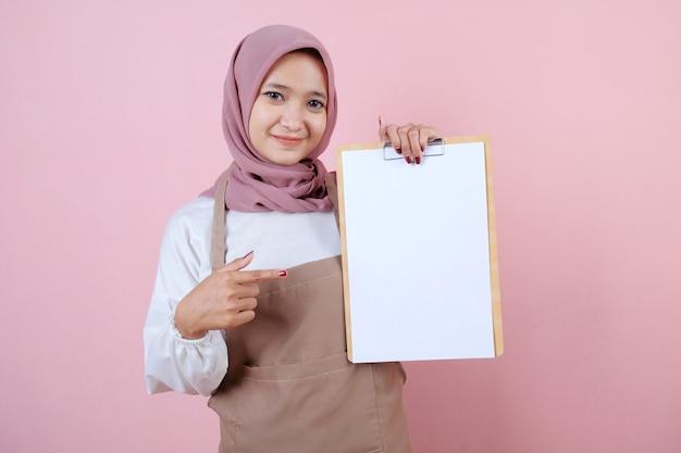 Piękna młoda kobieta ubrana w fartuch z uśmiechem i szczęśliwym menu książki