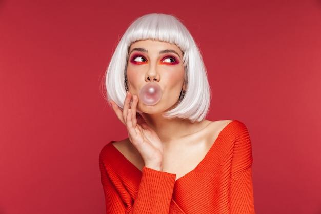 Piękna młoda kobieta ubrana w jasny makijaż i białą perukę stojącą odizolowaną na różowej, żującej gumie do żucia