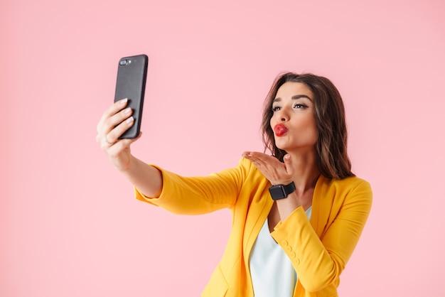 Piękna młoda kobieta ubrana w kolorowe ubrania, stojąc na białym tle nad różowym, biorąc selfie