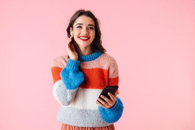 Piękna młoda kobieta ubrana w kolorowe ubrania stojący na białym tle nad różowym, słuchanie muzyki przez słuchawki, trzymając telefon komórkowy