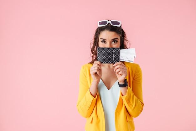 Piękna młoda kobieta ubrana w kolorowe ubrania stojących na białym tle nad różowym, pokazując paszport z biletami lotniczymi